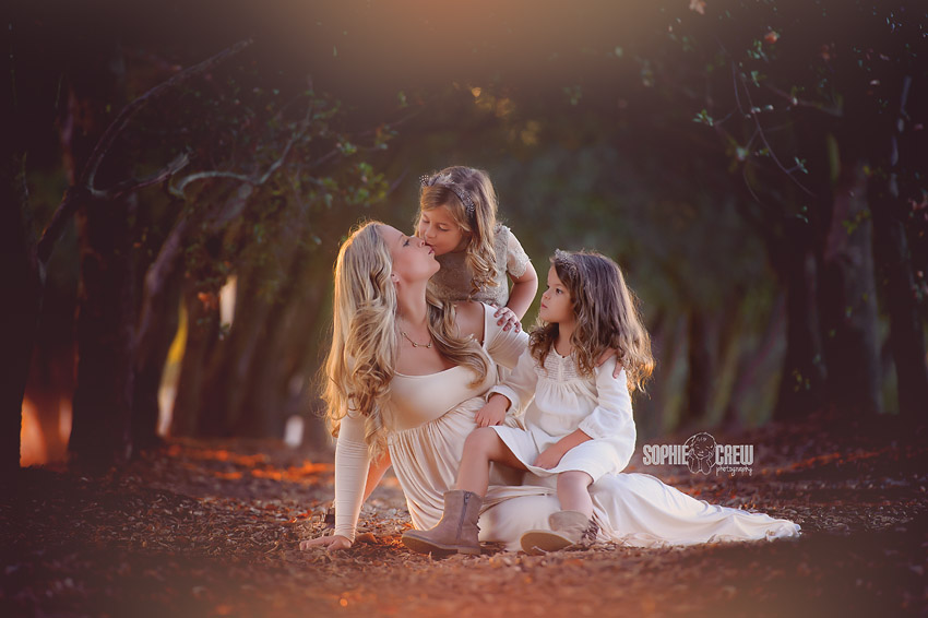 Mother and two daughters sit under Hallway of Trees and pose for Sophie Crew Photography.  Nature session with San Diego professional maternity and newborn photographer