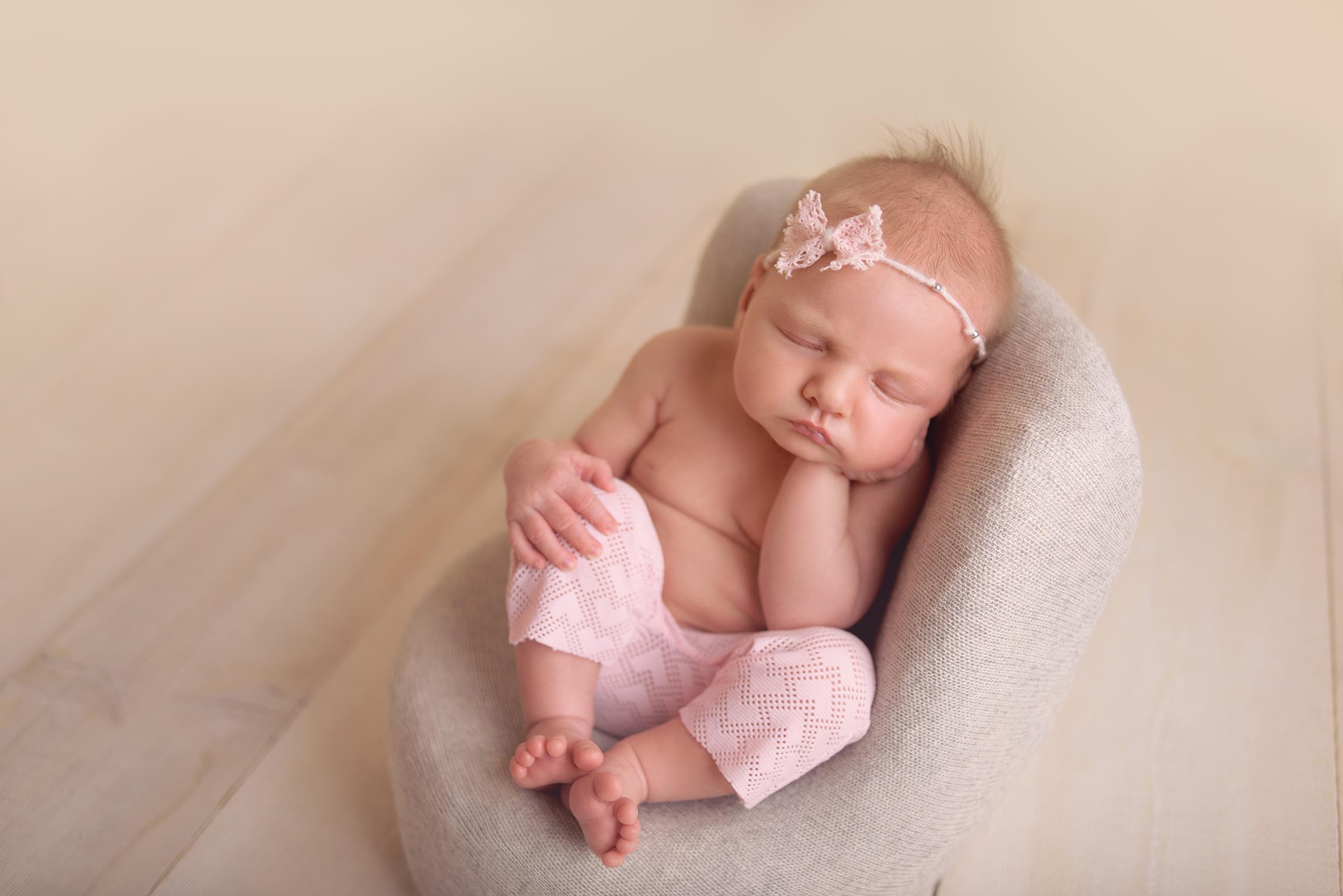 Newborn girl sitting in DIY newborn prop chair