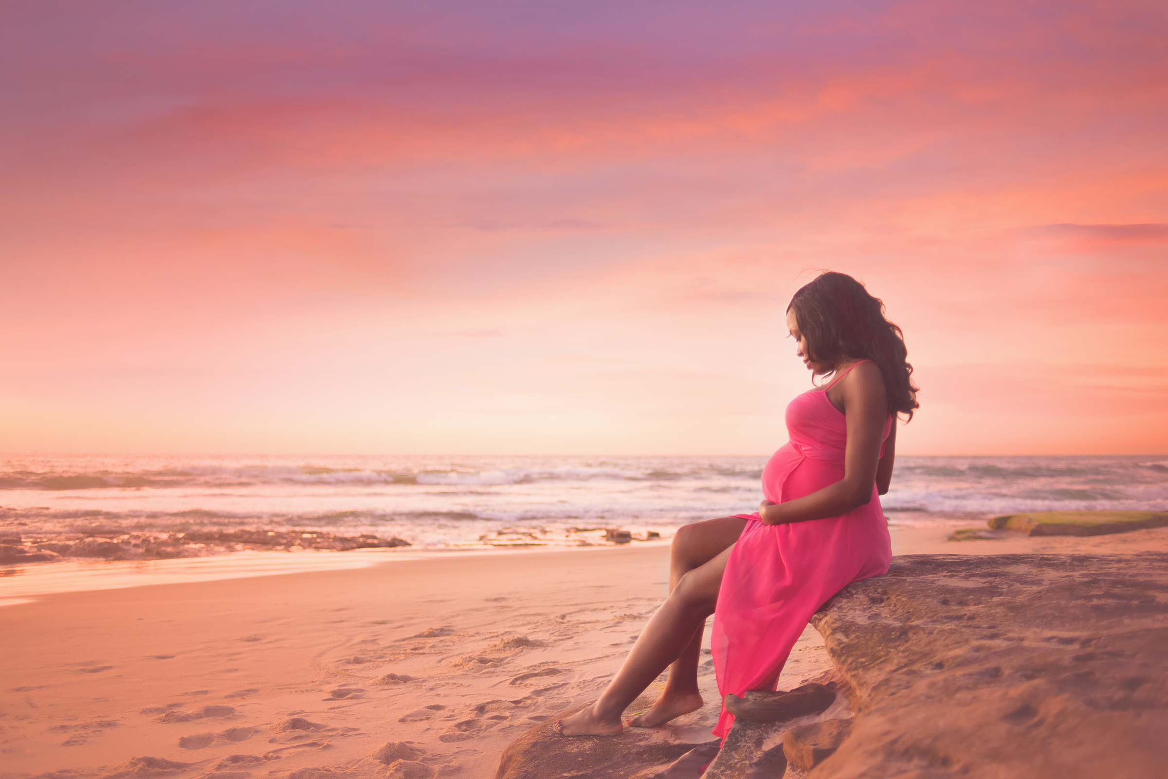 Stunning maternity photo session at sunset with colorful skies in San Diego beach