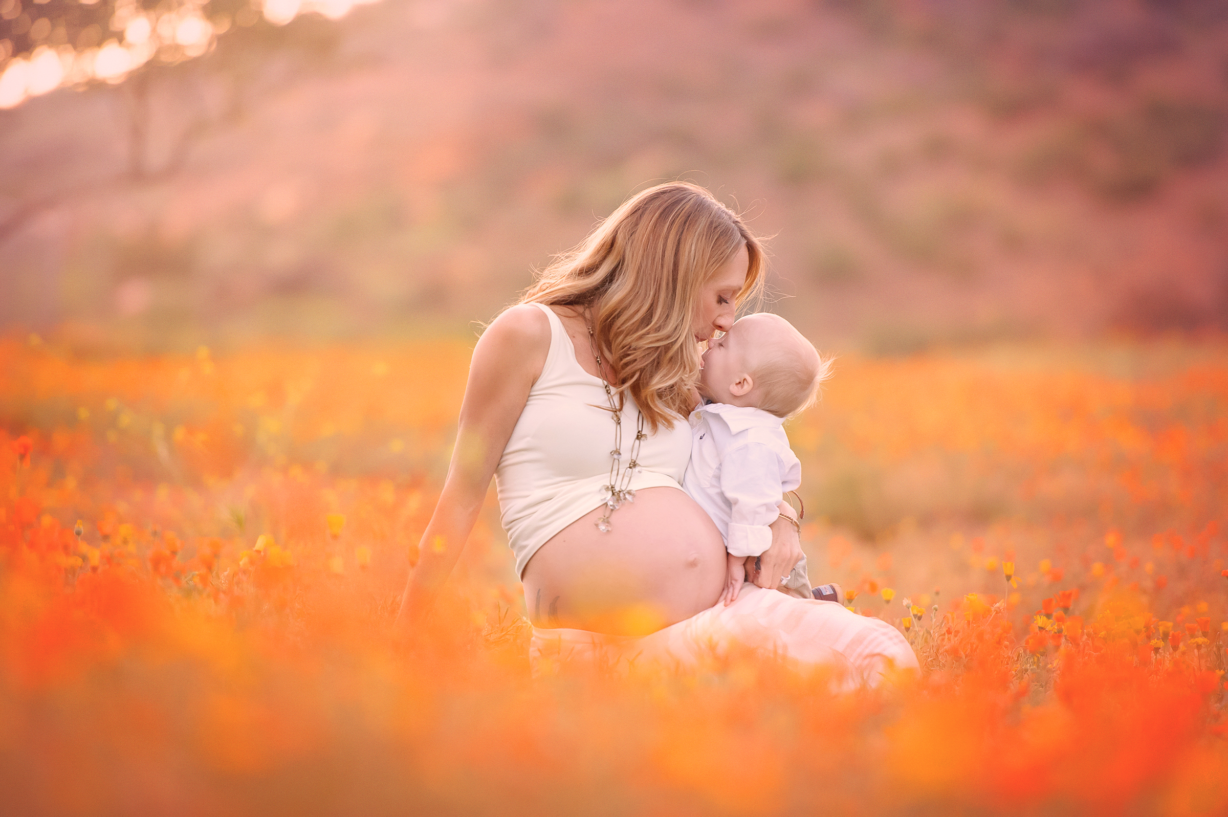 Pregnancy photos in orange flower field in San Diego, CA