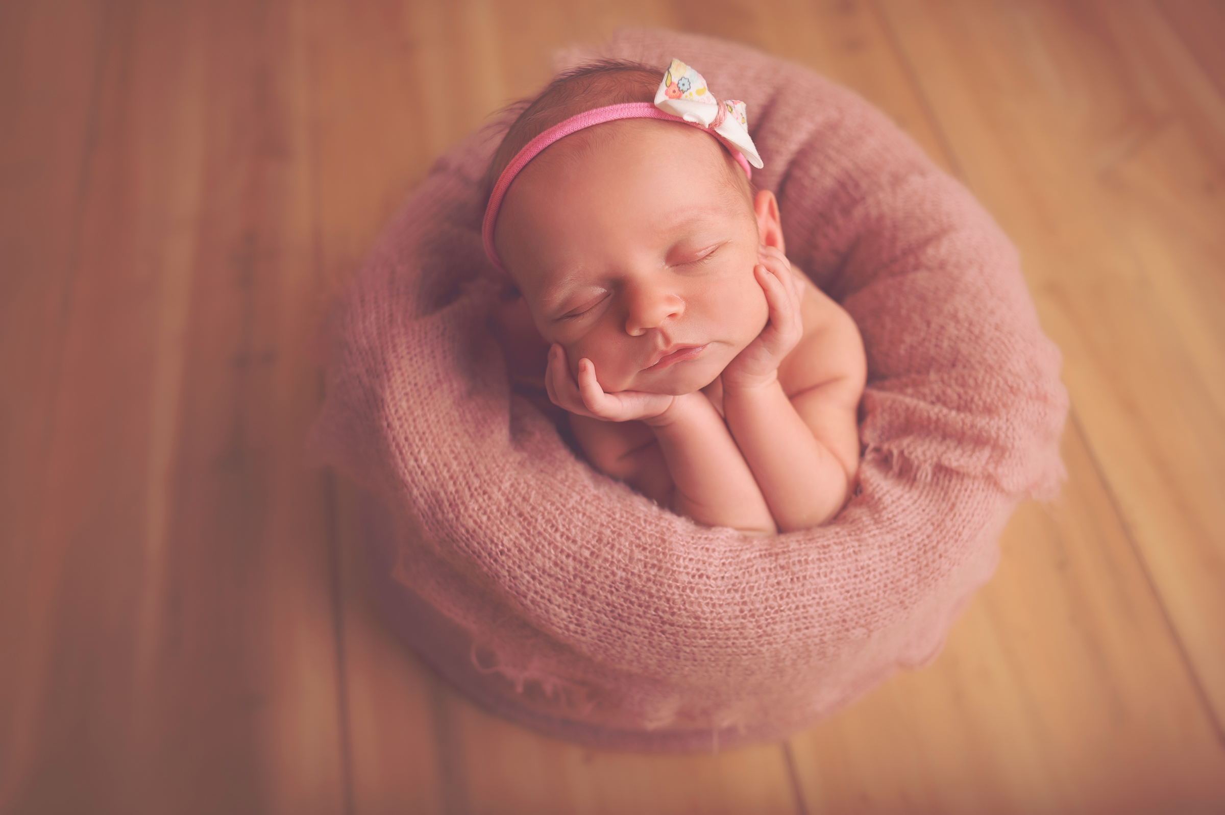 Peaceful newborn girl in pink pose during photo session in California baby studio.