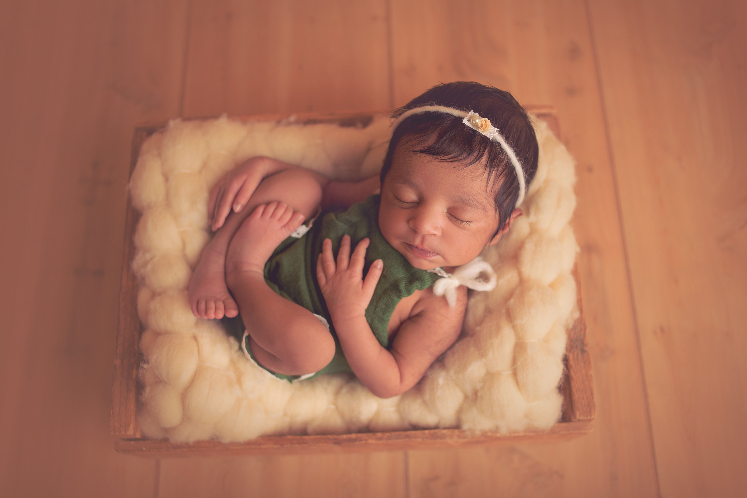 Newborn girl posed in wooden crate for her infant photo session in San Diego, California