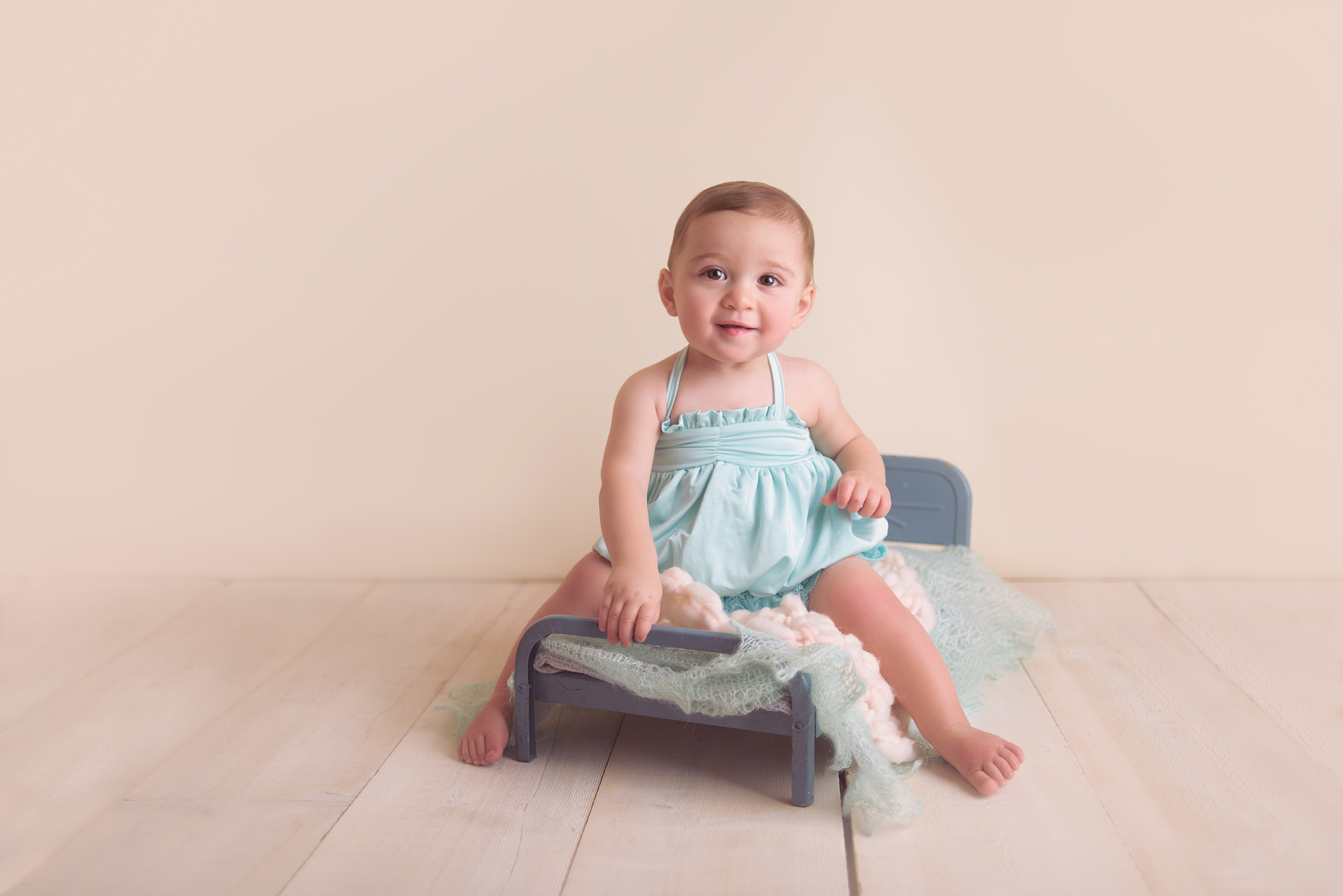 Baby girl sitting on on vintage doll bed for one year old portrait photography session in studio San Diego