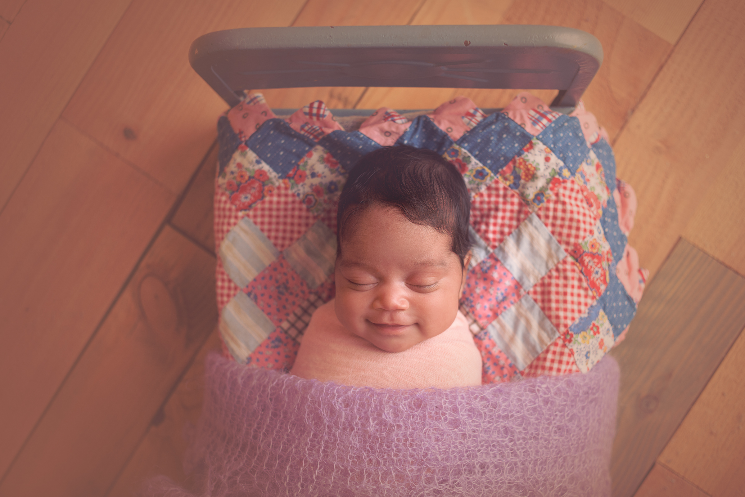Happy baby girl sleeping in vintage blue doll bed for photography newborn session