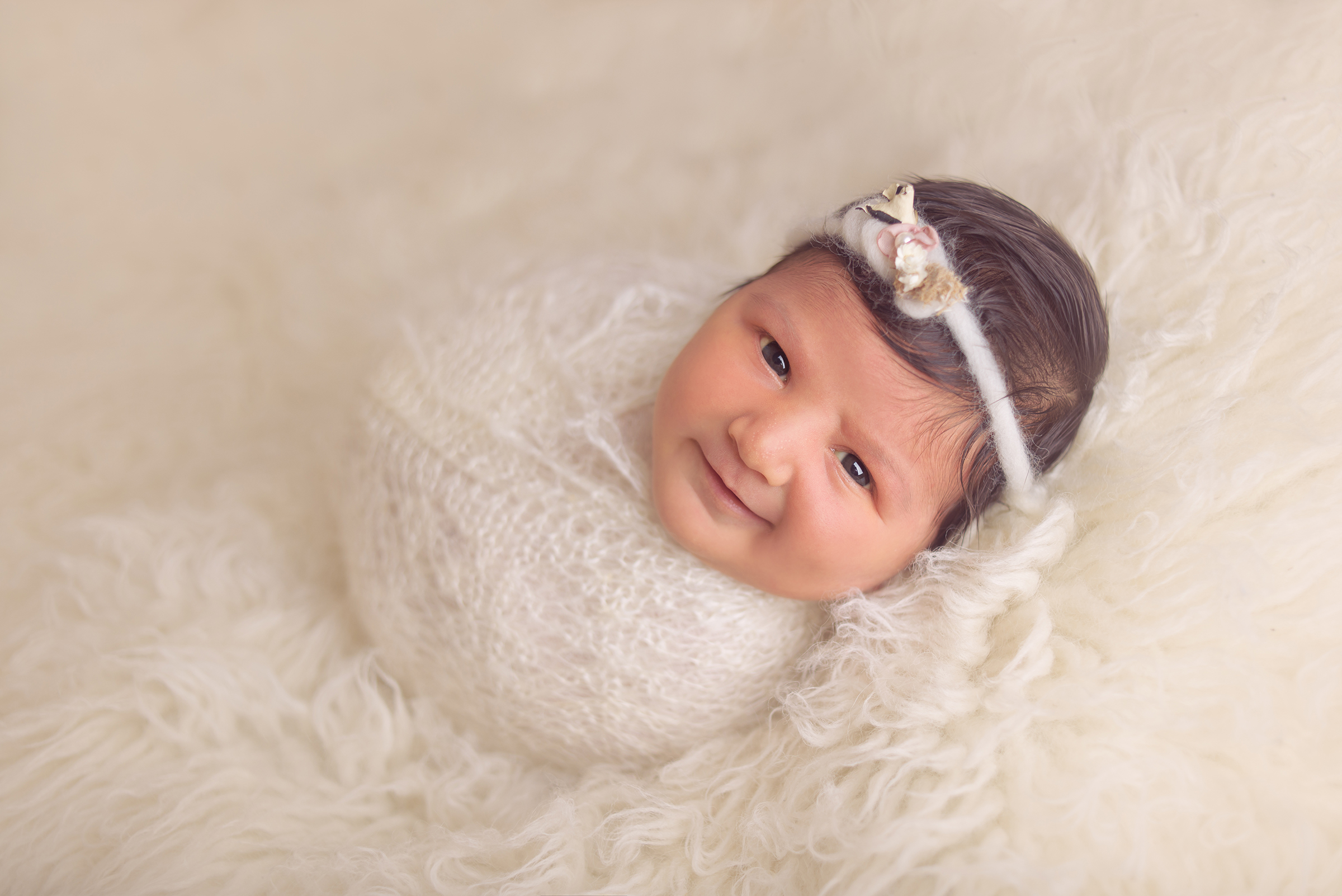 Sweet infant newborn swaddled for her newborn photography studio session in San Diego