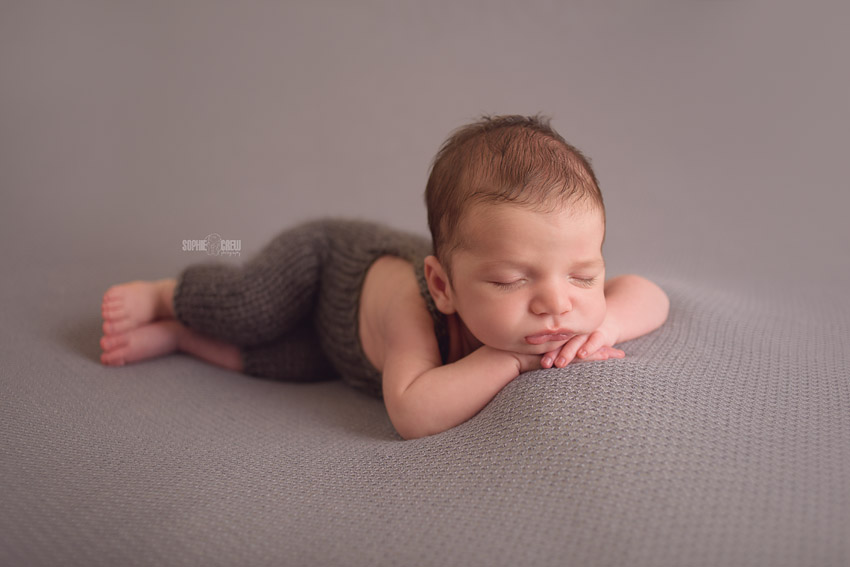 Newborn boy with long lashes wearing a knit grey romper on a grey backdrop blanket.