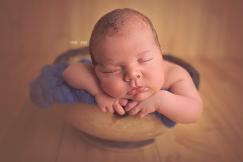 Newborn boy posed in a round, wooden bowl with his head propped on his arms