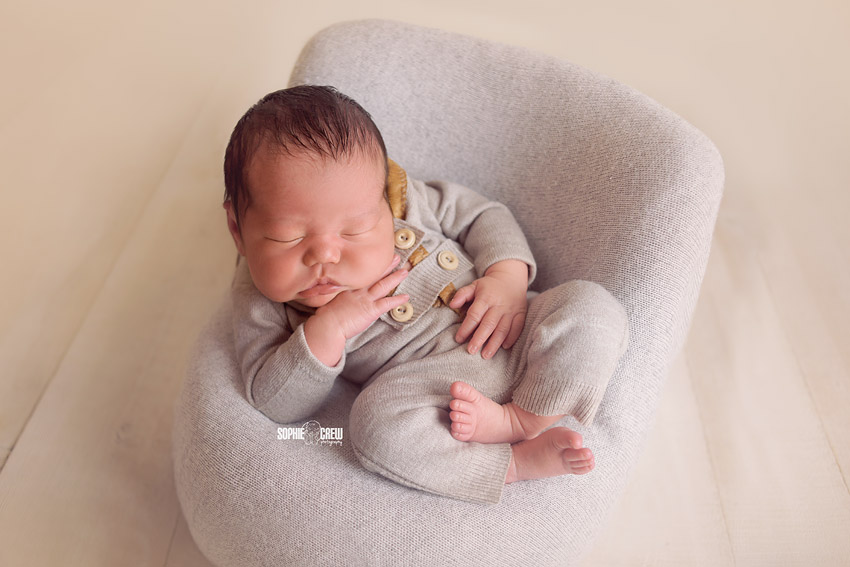 Newborn posed on DIY posing pod with with gray tones