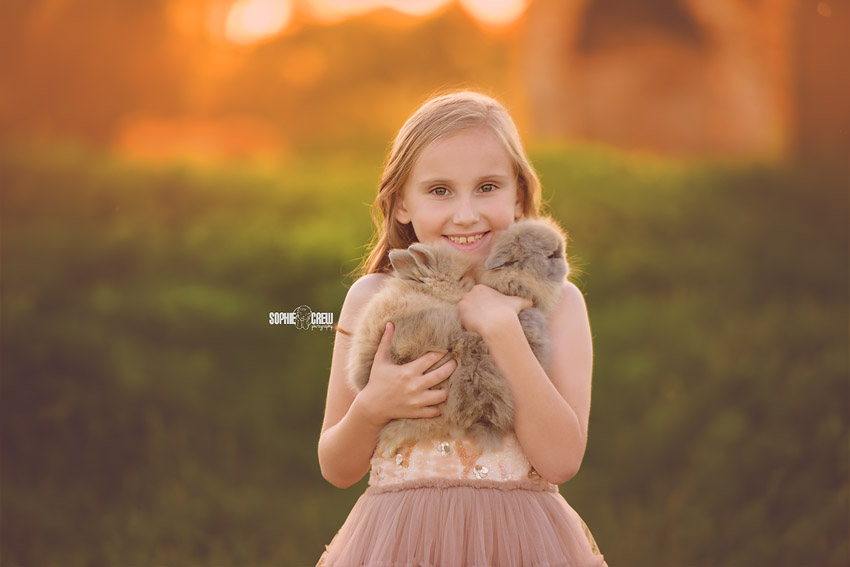 Girl holds two baby bunnies during San Diego photography mini session with Sophie Crew