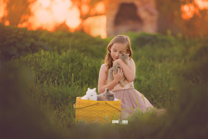 Little girl snuggles with live bunnies for photography session in San Diego