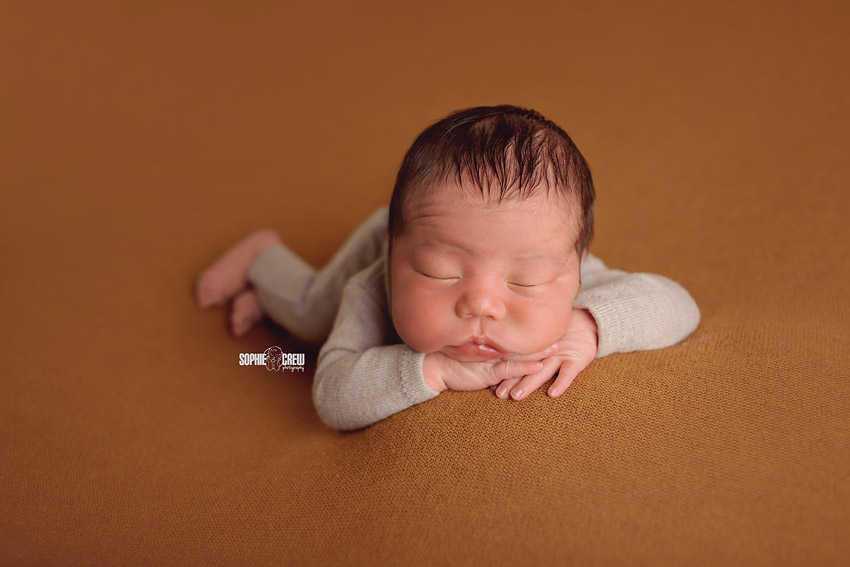 Newborn head resting on arms pose