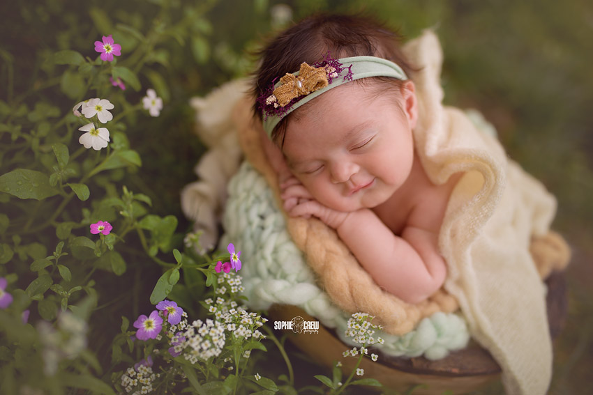 newborn posed outdoors smiles among wildflowers during her infant photography session