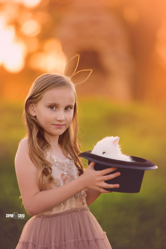 Child with bunny ear headband holds a magic bunny in a hat for photography in San Diego