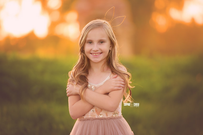 Little girl smiles during her photo session at a fireplace location in San Diego, CA