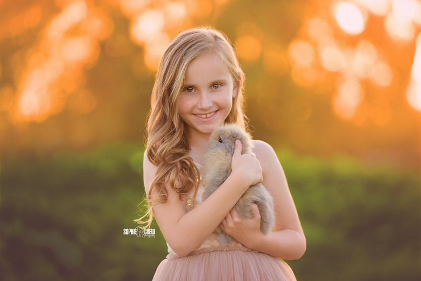 Child holding a gray and brown baby bunny in San Diego