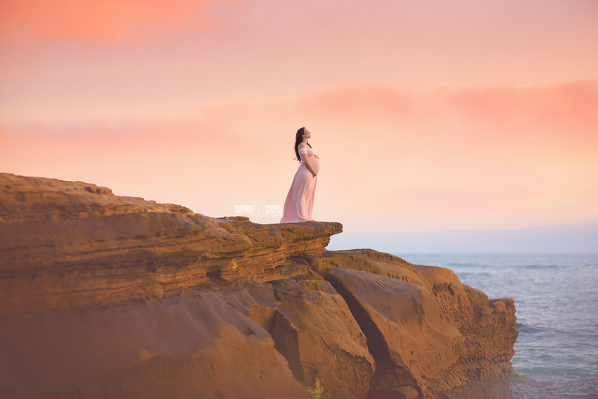 Gorgeous pregnant mother stands on cliff overlooking the Pacific Ocean in La Jolla, CA