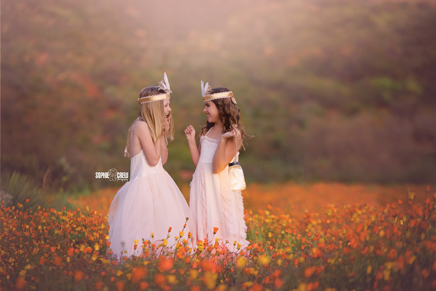 Two girls in Dollcake dresses in field of orange wildflower superbloom in San Diego