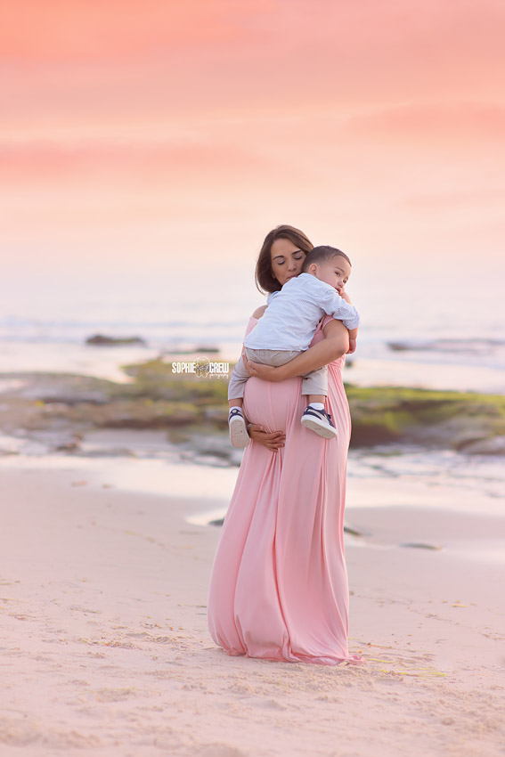 Expectant mother holds her son on beach during maternity photography session in San Diego