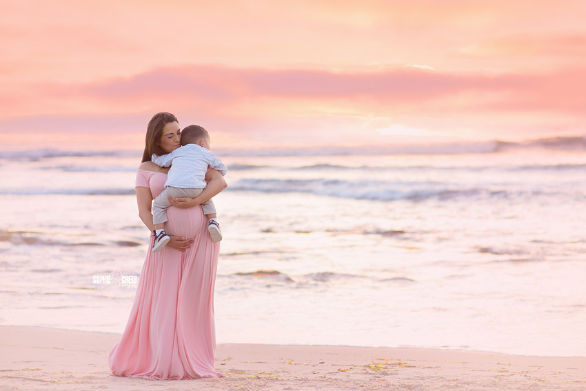 Mother to be holds her toddler son on beach for photography portraits with Sophie Crew Photography