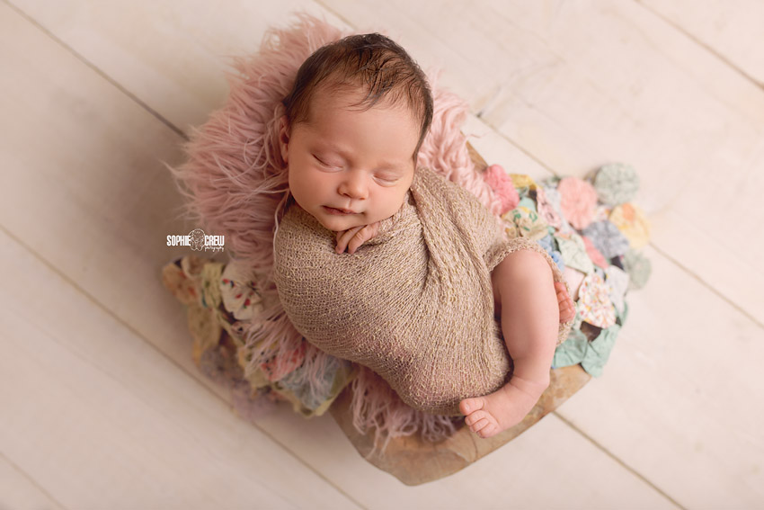 Newborn posed in neutral wrap with quilt and pink accents