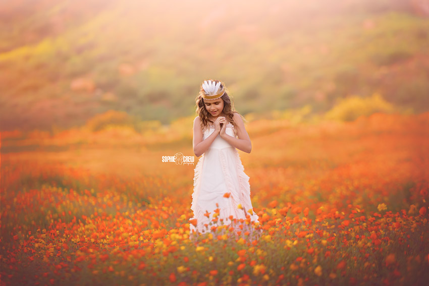 Girl dances in field of wildflowers in San Diego, CA