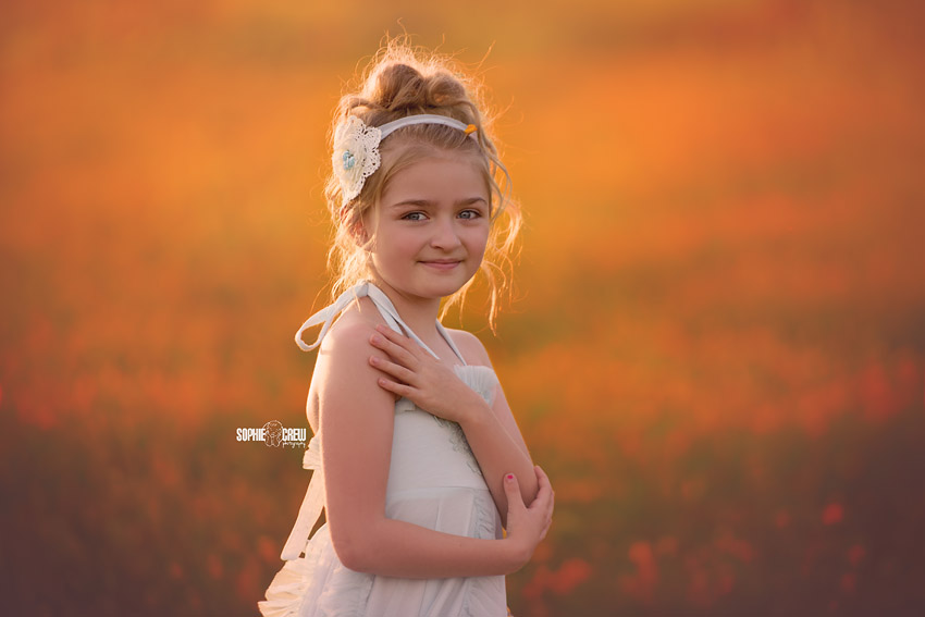 Little girl poses in a field of wild California poppies for her family mini portrait session in San Diego, CA