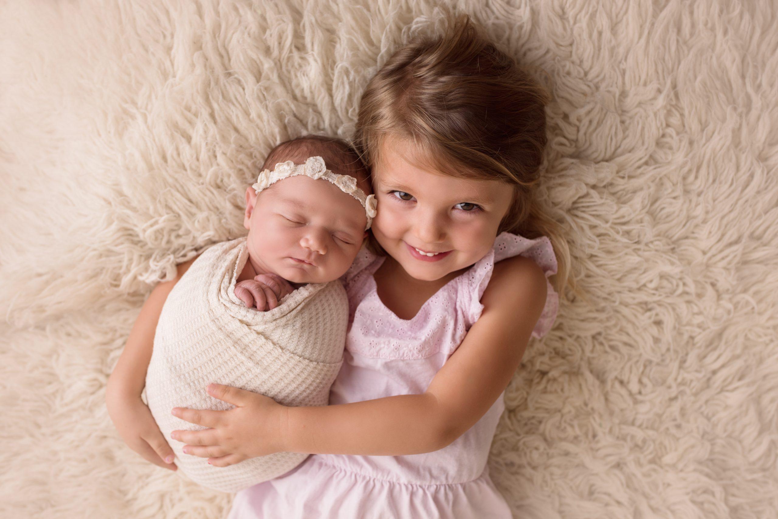 Newborn posed with big sister sibling poses on flokati rug