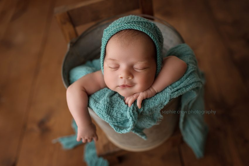 Newborn boy in vintage bucket newborn pose with teal colors